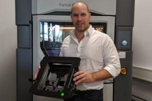 Stefan Kammann vor dem Fortus 450mc 3D-Drucker im ADaM Competence Center mit einer 3D-gedruckten, ESD-konformen Klebevorrichtung .jpg