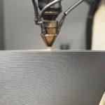 3D Metaldrucker produziert mit Laserauftragsschweißen ein Bauteil.