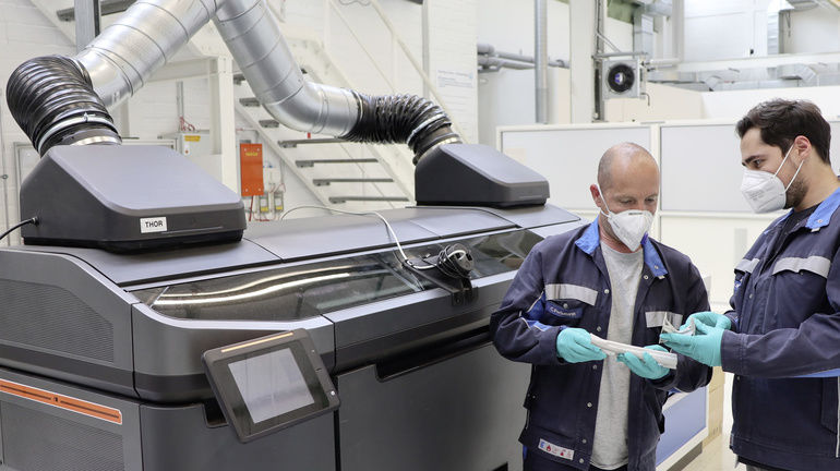 Two_Volkswagen_employees_check_the_quality_of_structural_parts_produced_using_the_binder_jetting_process_for_car_production_in_front_of_the_prototype_of_the_special_printer_at_the_high-tech_3D_printing_center_in_Wolfsburg.